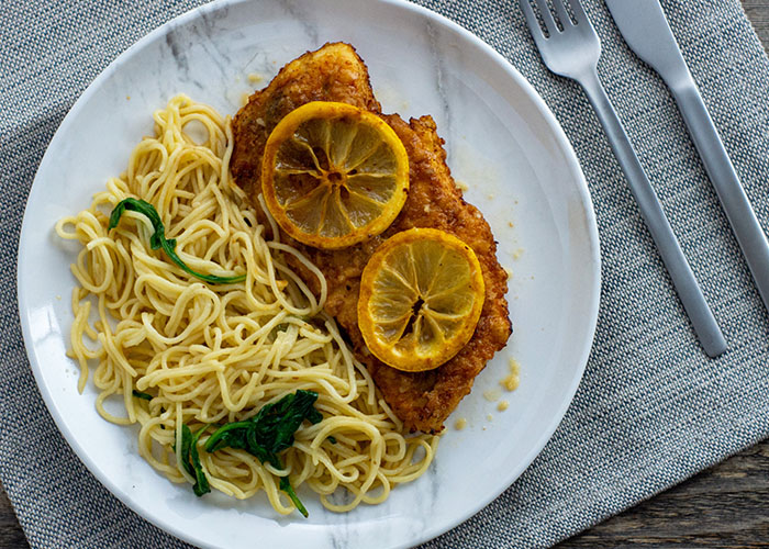 Chicken francese topped with sliced lemons next to angel hair pasta on a round white plate with stainless steel silverware in the back on a grey placemat all on a wooden surface