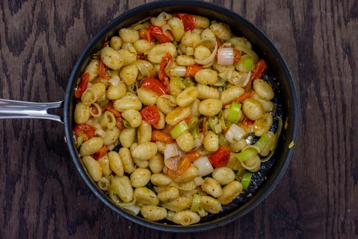 Sliced leek, tomato, and garlic with melted butter and white wine mixed with gnocchi in a skillet on a wooden surface