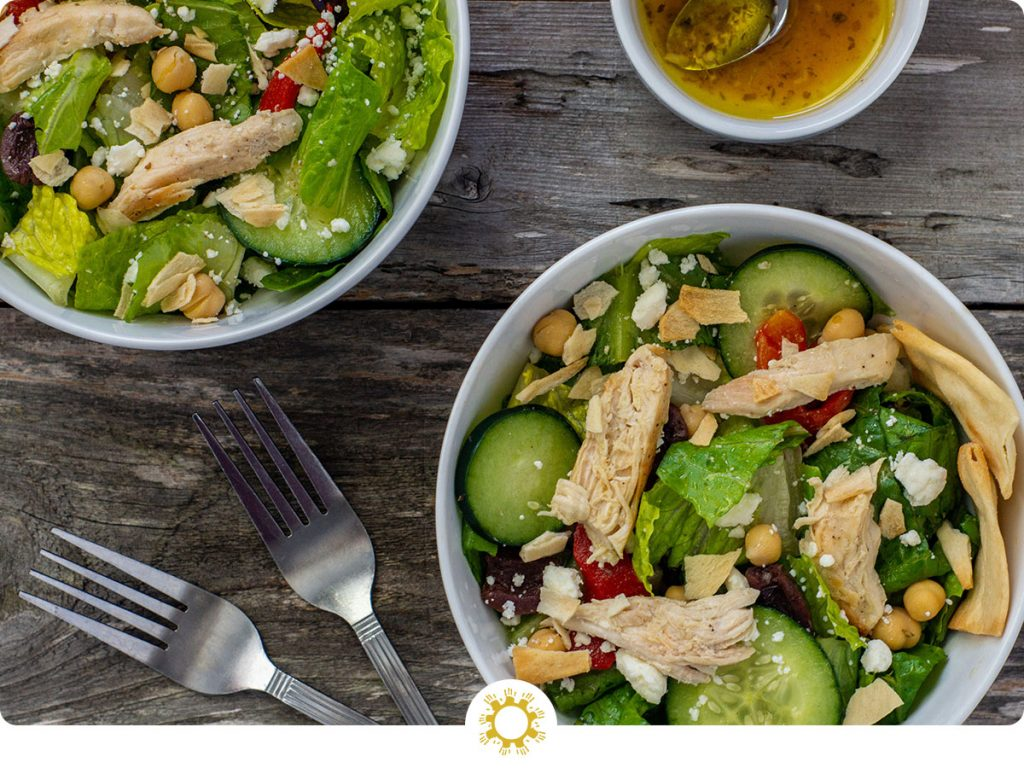 Two bowls of Greek chicken salad next to a smaller bowl of dressing with a spoon and a fork next to the bowls all on a wooden surface (with logo overlay)