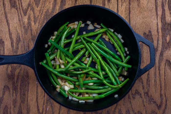 Green beans and onions in a cast-iron skillet on a wooden surface