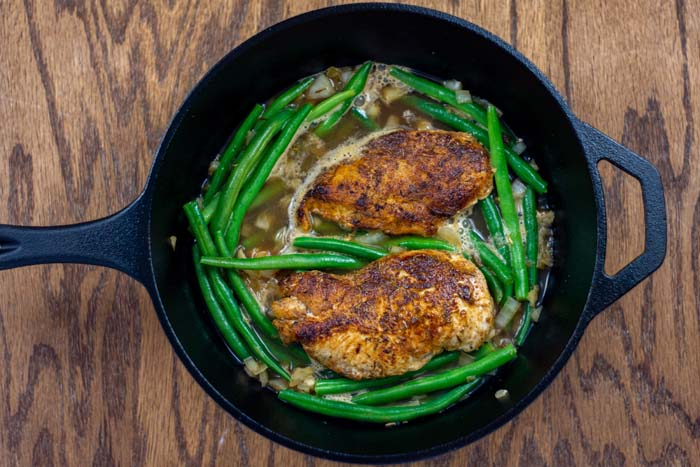 Chicken and vegetables with broth in a cast-iron skillet on a wooden surface