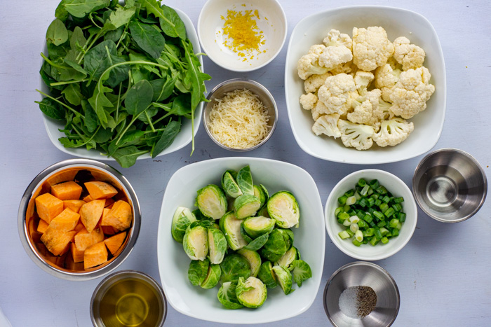 Ingredients for roasted vegetable salad in stainless steel and white bowls on a white surface