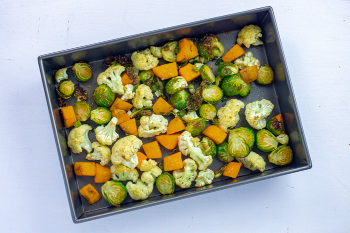 Roasted vegetable mix on a baking pan on a white surface