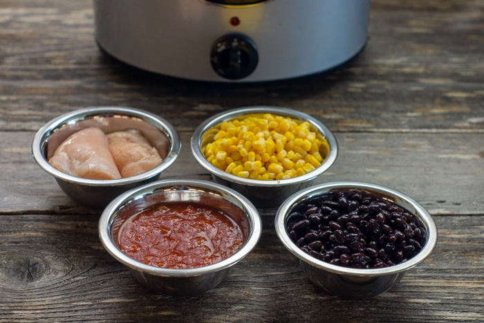 Ingredients for salsa chicken in stainless steel bowls in front of a slow cooker on a wooden surface
