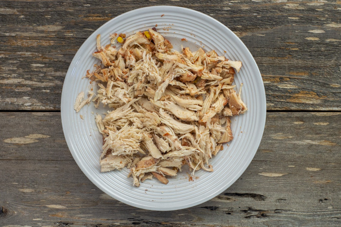 Shredded chicken on a round white plate on a wooden surface