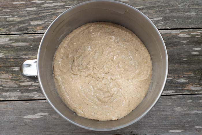Banana bread pancake batter in a stainless steel mixing bowl on a wooden surface
