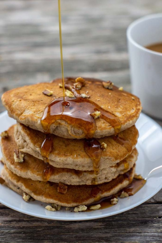 Pile of banana bread pancakes topped with chopped pecans on a round white plate with syrup being dripped on top with a white mug of coffee behind all on a wooden surface (vertical)