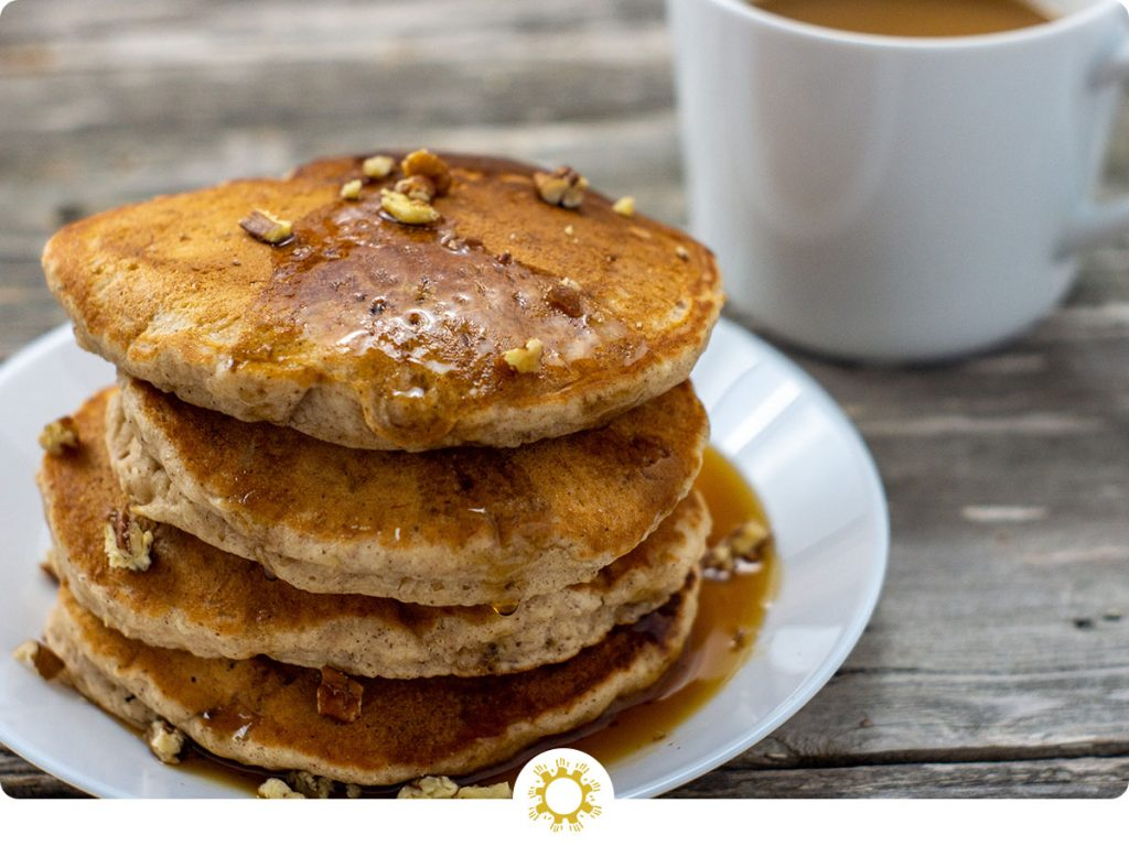 Pile of banana bread pancakes topped with chopped pecans on a round white plate with syrup being dripped on top with a white mug of coffee behind all on a wooden surface (with logo overlay)