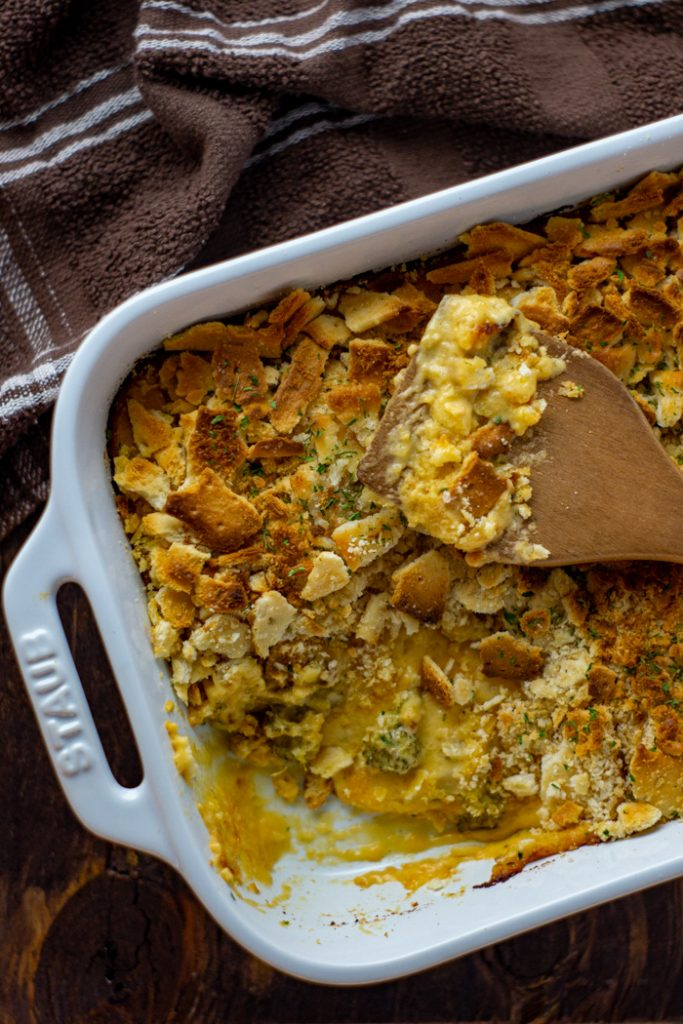 Broccoli and cheese casserole topped with crushed crackers with a wooden spoon in a white casserole dish with a brown and white cloth all on a wooden surface (vertical)