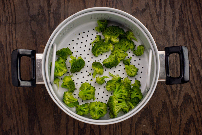 Steamed broccoli in a steamer basket on a wooden surface