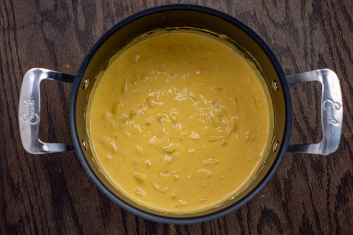Cheese mixed in a stockpot on a wooden surface