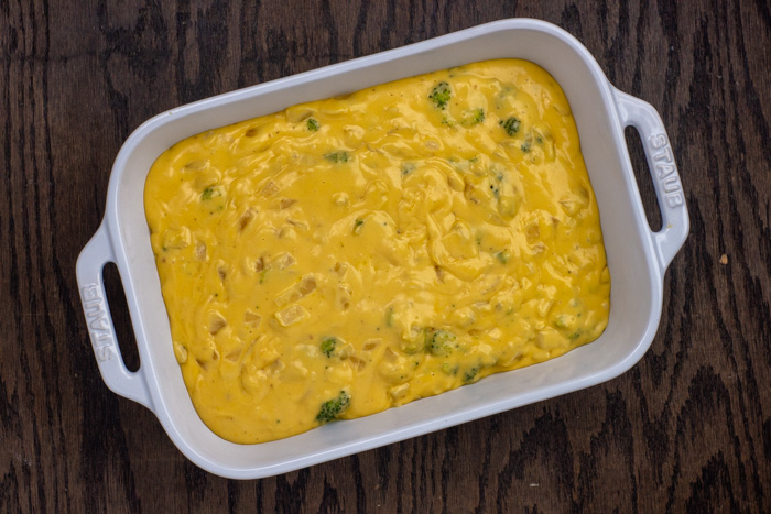 Broccoli and cheddar casserole in a white casserole dish on a wooden surface