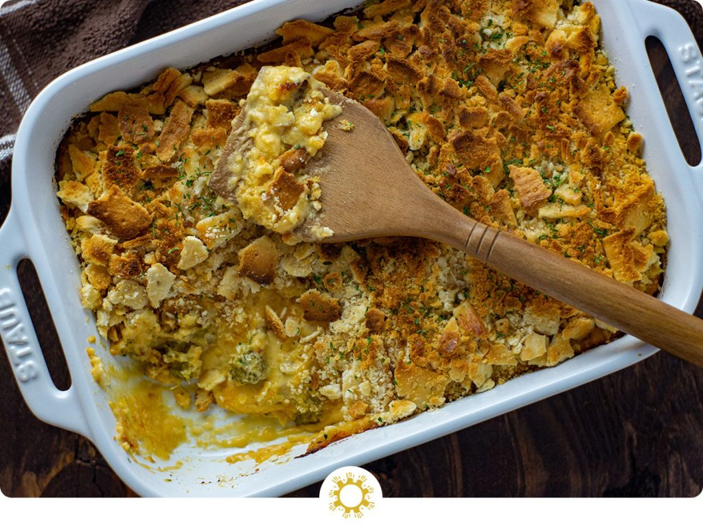 Broccoli and cheese casserole topped with crushed crackers with a wooden spoon in a white casserole dish with a brown and white cloth all on a wooden surface (with logo overlay)