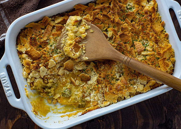 Broccoli and cheese casserole topped with crushed crackers with a wooden spoon in a white casserole dish with a brown and white cloth all on a wooden surface