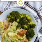 Chicken with artichoke sauce garnished with dill next to steamed broccoli on a round white plate with a white and brown towel behind all on a wooden surface (with title overlay)