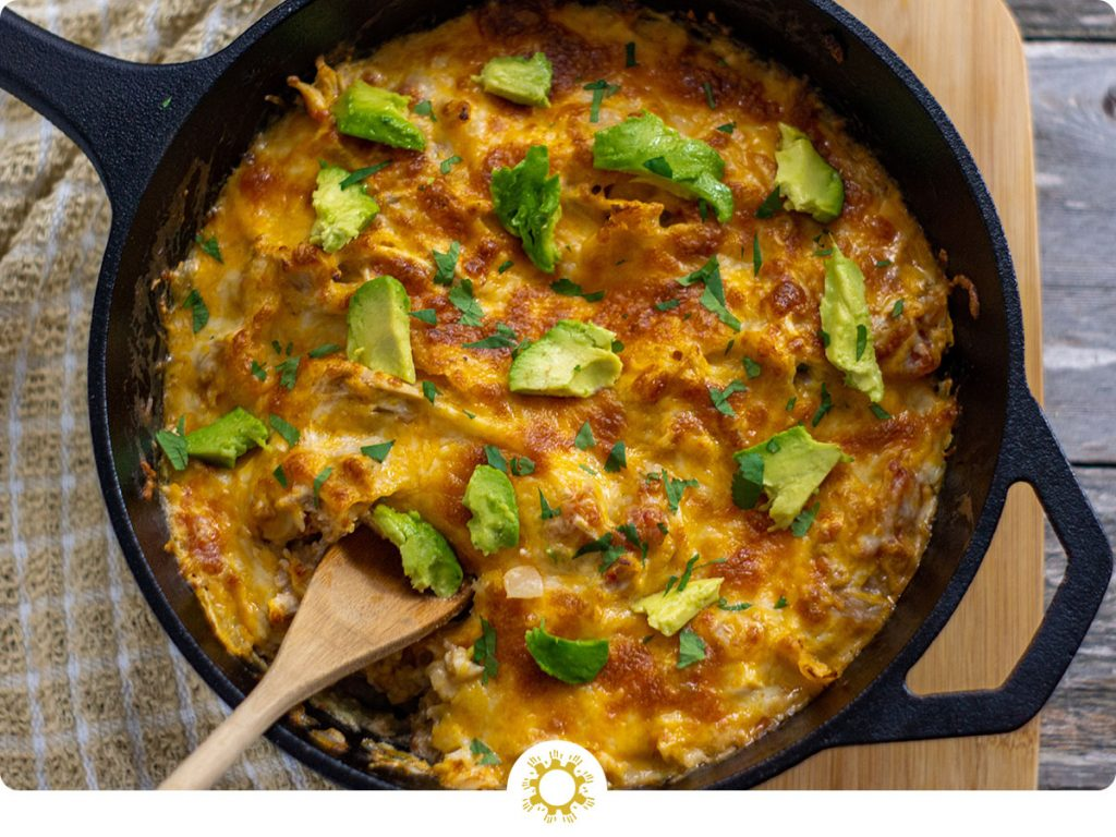 Chicken enchilada suizas topped with sliced avocado and cilantro with a wooden spoon in a cast iron skillet on a wooden surface (with logo overlay)