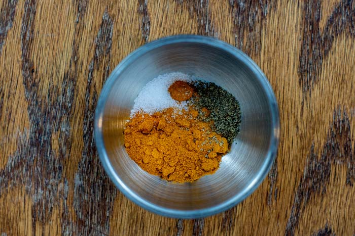 Turmeric and seasonings in a small stainless steel bowl on a wooden surface