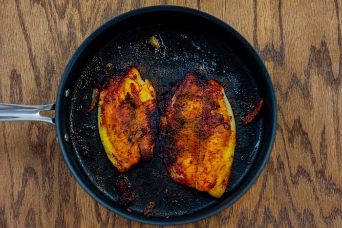 Two tilapia fillets seasoned in a skillet on a wooden surface