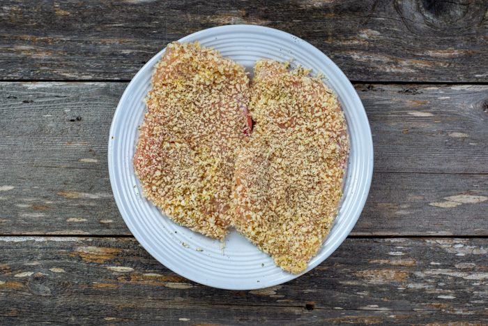 Flattened chicken breast with seasonings covered with panko bread crumbs on a round white plate on a wooden surface