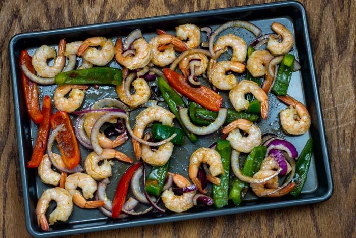 Shrimp fajita filling ingredients spread out on a metal baking sheet on a wooden surface