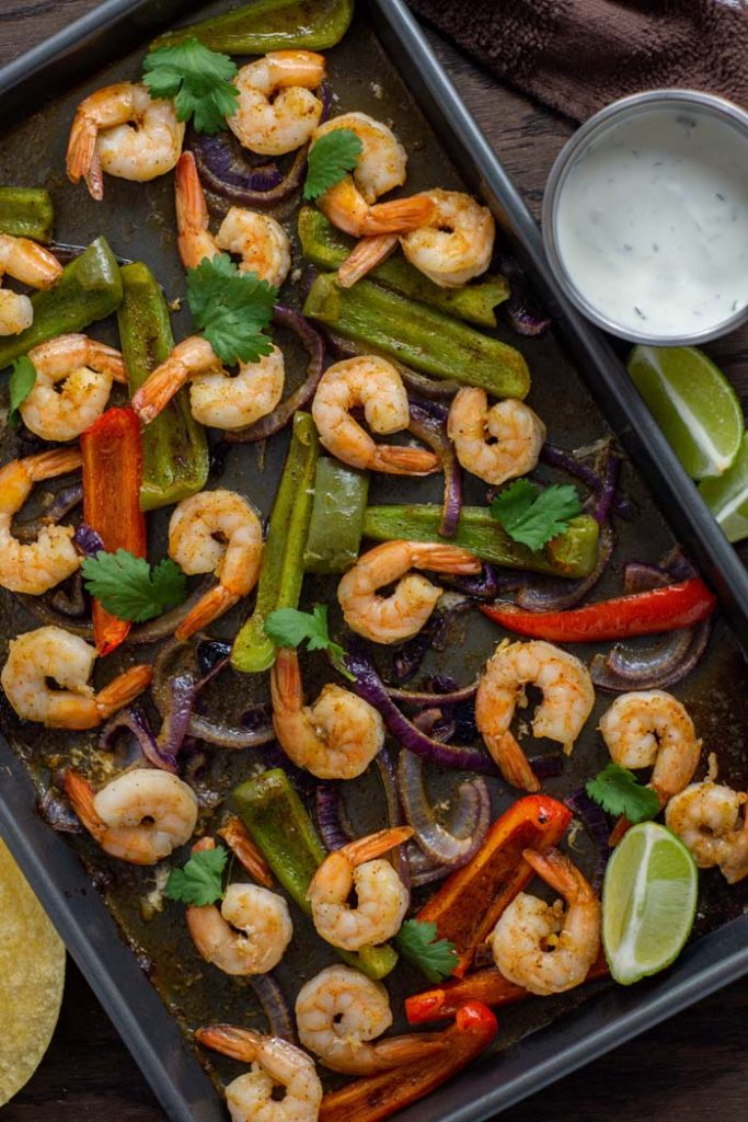 Shrimp and roasted vegetables for shrimp fajitas on a metal baking sheet next to a stainless steel bowl of sour cream sauce with lime wedges and corn tortillas to the side and a brown towel behind all on a wooden surface (vertical)