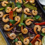 Shrimp and roasted vegetables for shrimp fajitas on a metal baking sheet next to a stainless steel bowl of sour cream sauce with lime wedges and corn tortillas to the side and a brown towel behind all on a wooden surface