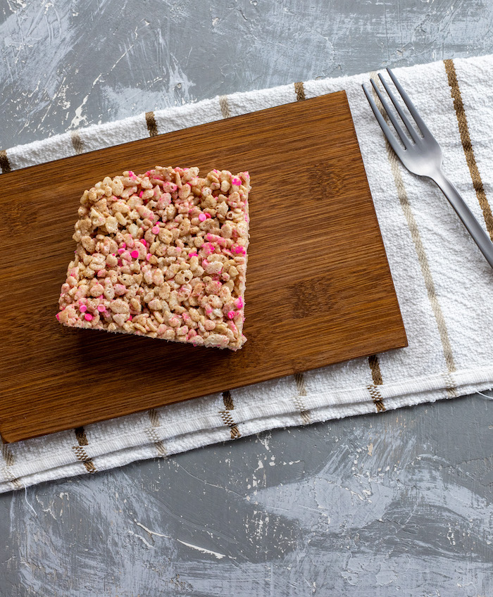 Square piece of sprinkled rice krispies on a bamboo platter with a stainless steel fork on a white and brown towel all on a grey and white surface (vertical)