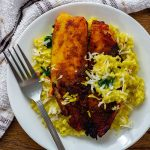 Coconut-Turmeric Tilapia on a bed of shredded carrots and coconut rice topped with shredded coconut with a stainless steel fork on a round white plate with a white and brown towel behind all on a wooden surface