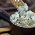 Woman's hand dipping a graham cracker into a brown bowl of cookies and cream dip with graham crackers around the bowl and a brown towel behind all on a wooden surface (with title overlay)