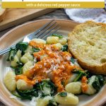 Gnocchi with spinach and red pepper sauce with a piece of cheesy garlic bread on a round plate with a bamboo tray of garlic bread behind next to a white and brown towel all on a wooden surface (with title overlay)