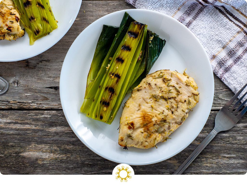 Lemon-Rosemary chicken with grilled leeks on a round white plate with another plate and white and brown towel behind and a stainless steel fork in front all on a wooden surface (with logo overlay)