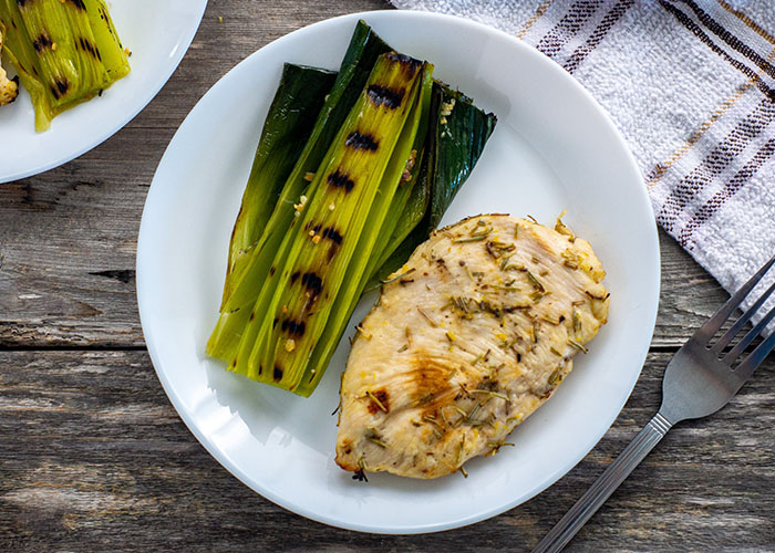 Lemon-Rosemary chicken with grilled leeks on a round white plate with another plate and white and brown towel behind and a stainless steel fork in front all on a wooden surface