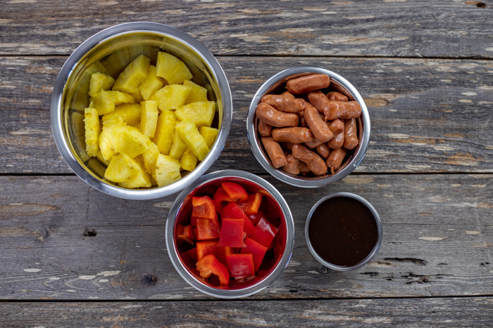 Ingredients for Hawaiian Lit'l Smokies in stainless steel bowls on a wooden surface: pineapple, sausages, marinade, and red bell pepper