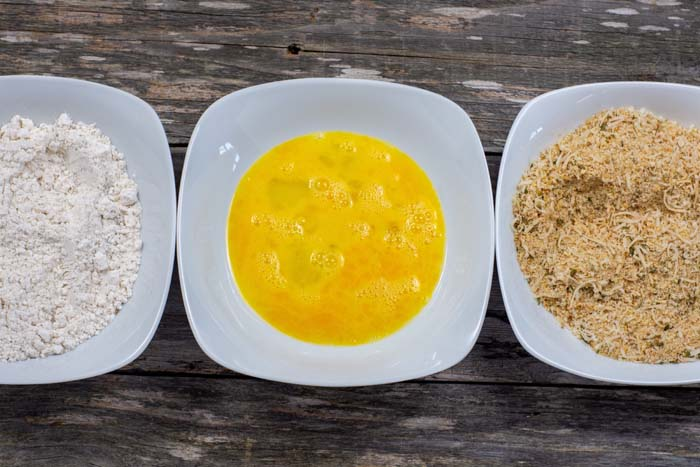 Three white bowls with flour in one, egg in the middle, and breadcrumbs in the last all on a wooden surface