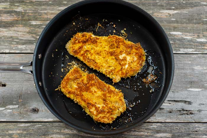 Parmesan crusted chicken in a cast-iron skillet on a wooden surface