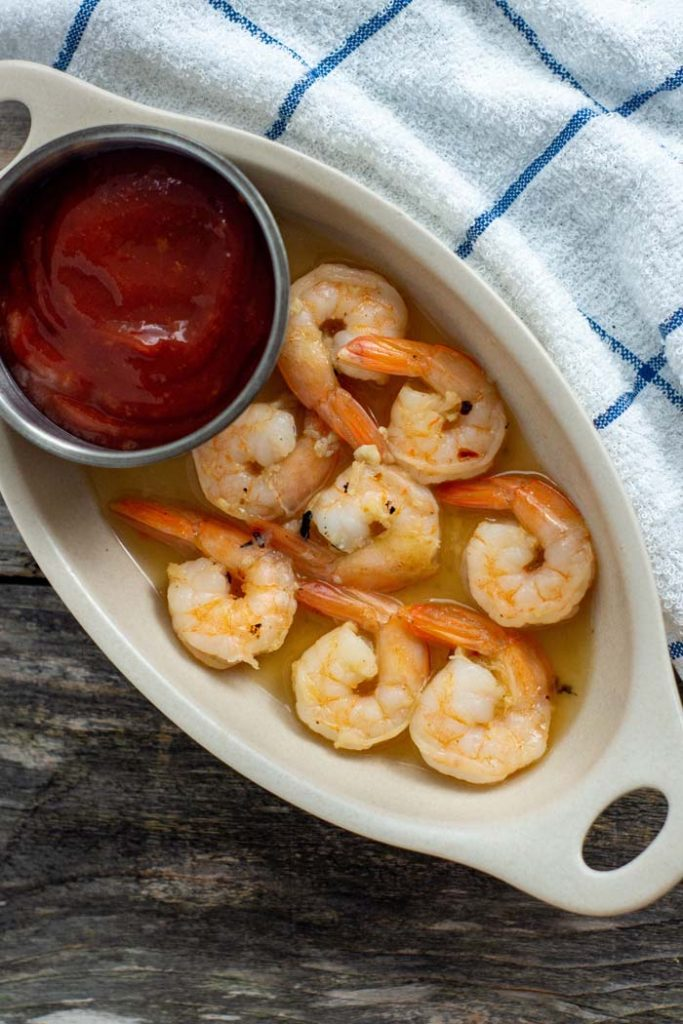 Roasted shrimp in a white oval dish with a small stainless steel bowl of sriracha cocktail sauce next to a white and blue towel on a wooden surface (vertical)