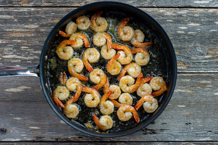 Shrimp cooking in oil in a skillet on a wooden surface