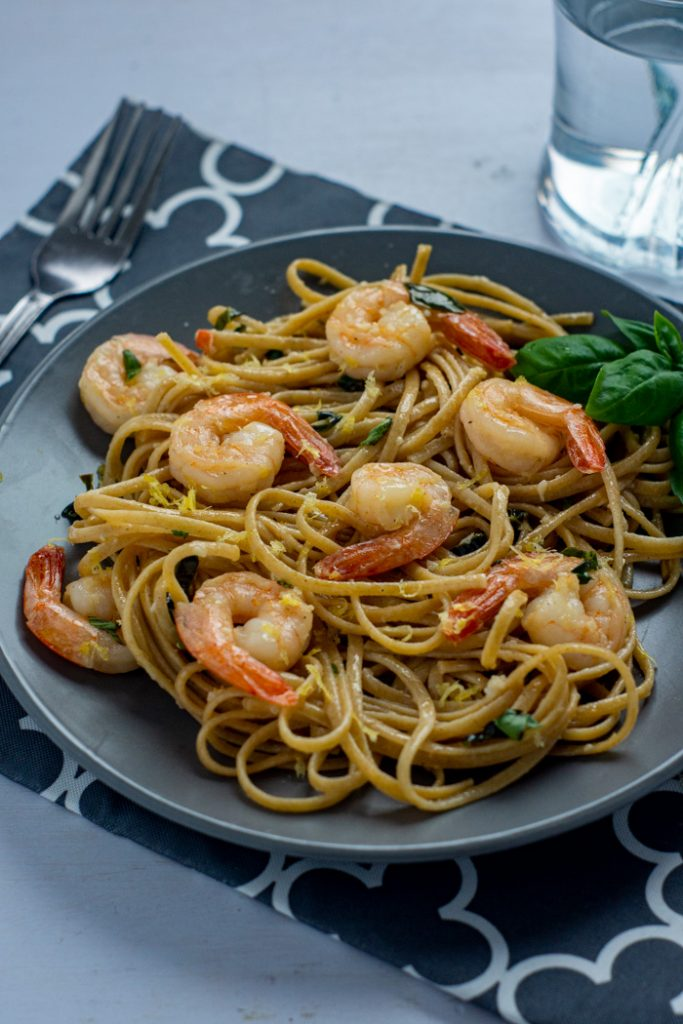 Shrimp scampi with basil on a round gray plate on top of a grey and white placemat with a stainless steel fork and a glass of water all on a white surface (vertical)