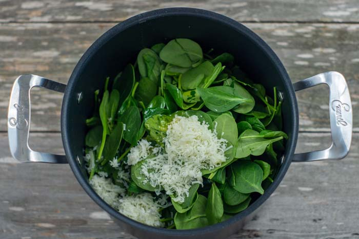 Spinach and shredded cheese in a lark stockpot on a wooden surface