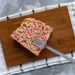 Square piece of sprinkled rice krispies on a bamboo platter with a stainless steel fork on a white and brown towel all on a grey and white surface