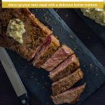 Cooked sliced steak topped with garlic-herb butter on a dark slate platter next to a steak knife with a slate platter of garlic-herb butter behind all on a dark wooden surface (with title overlay)