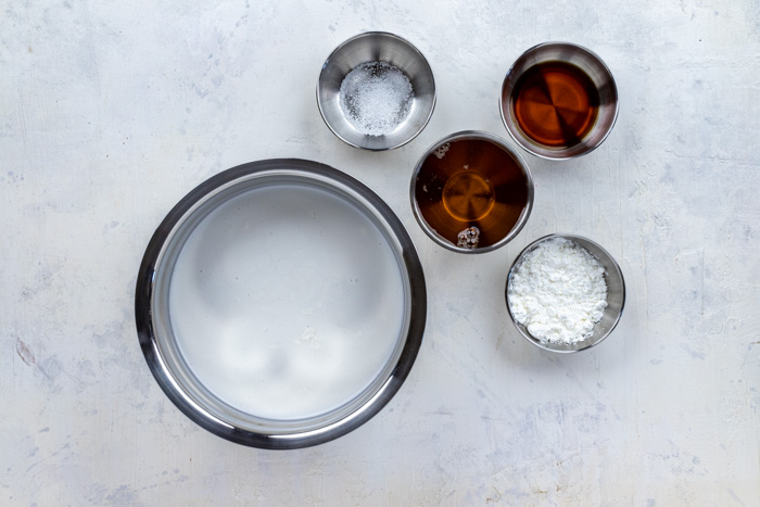 Ingredients for vegan coconut ice cream in stainless steel bowls on a white and grey surface