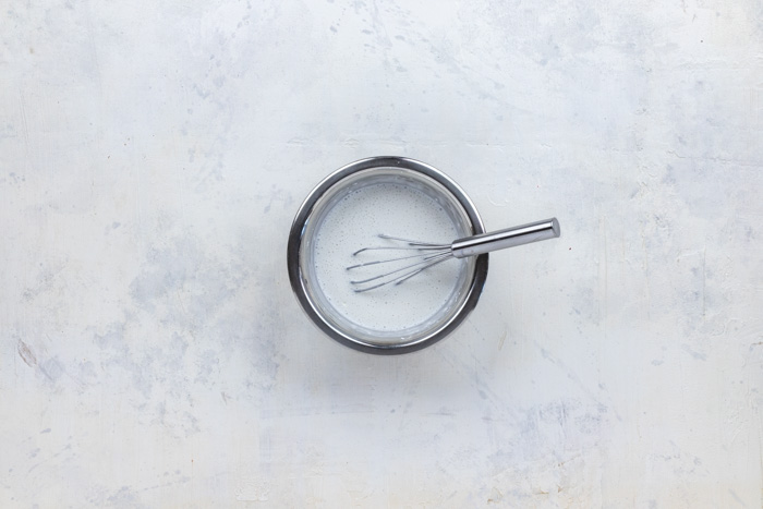 Whisked cornstarch and coconut milk with a wire whisk in a stainless steel bowl on a white and grey surface