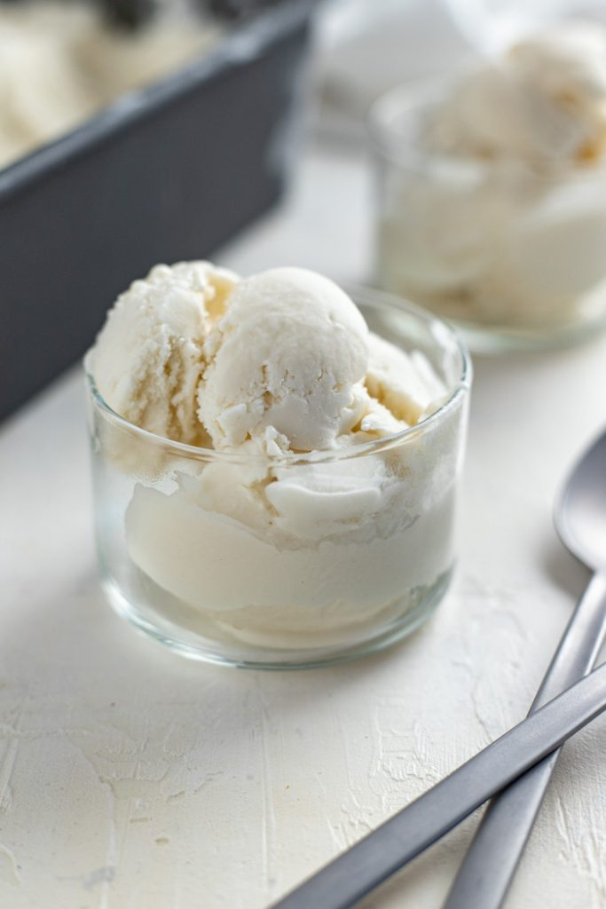 Vegan coconut ice cream in a small glass dish with another serving and a loaf pan of ice cream behind next to stainless steel spoons all on a white and grey surface (vertical)