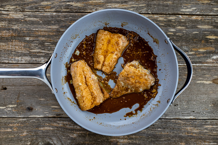Cooked salmon with orange ginger sauce in a skillet on a wooden surface