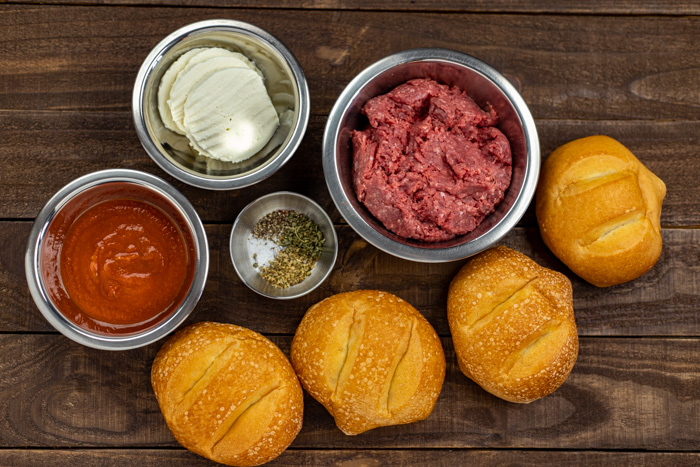 Ingredients for pizza burgers in stainless steel bowls on a wooden surface