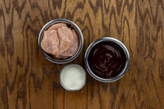 Ingredients for bbq ranch chicken in stainless steel bowls on a wooden surface