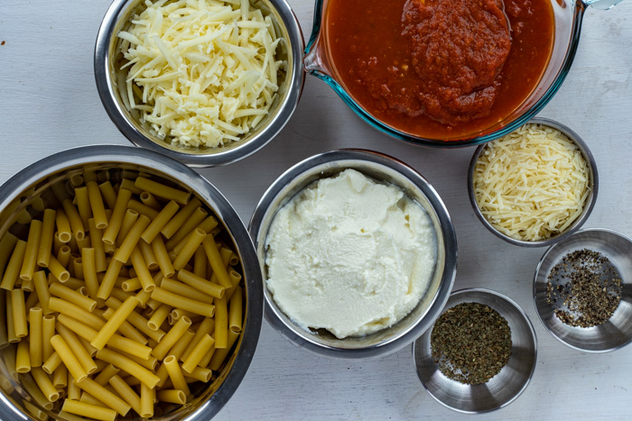 Ingredients for baked ziti in stainless steel bowls on a white wooden surface