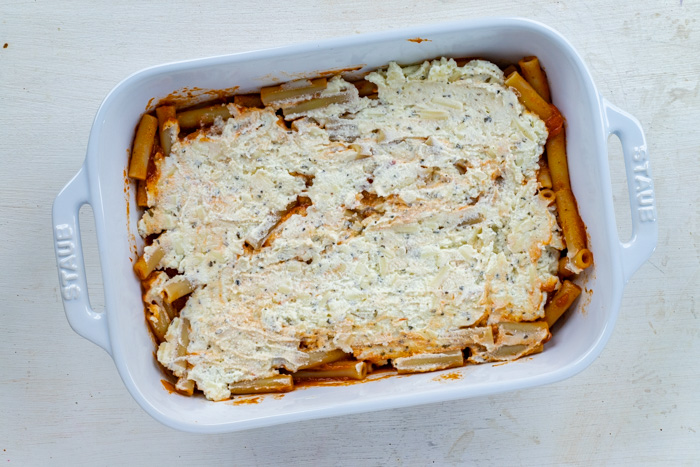Ziti noodles covered in sauce and cheese mixture in a white casserole dish on a white wooden surface