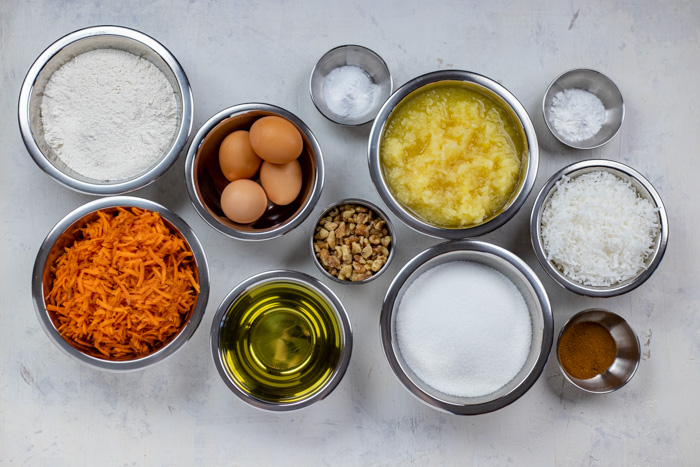 Ingredients for carrot cake in stainless steel bowls on a white wooden surface